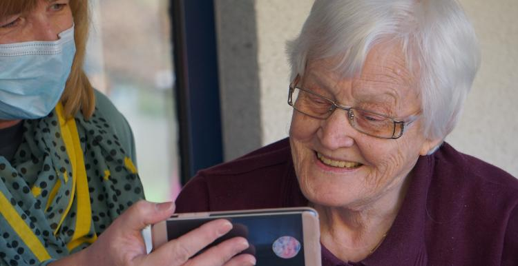 A younger woman shows a grey haired woman her phone screen