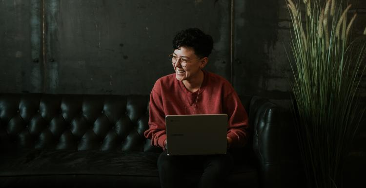 Young person sitting on a sofa and working on a laptop
