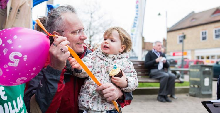 Grandpa with toddler holding a balloon