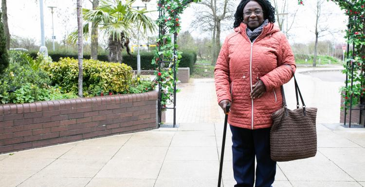Woman with walking stick, smiling and standing outside a hospital.
