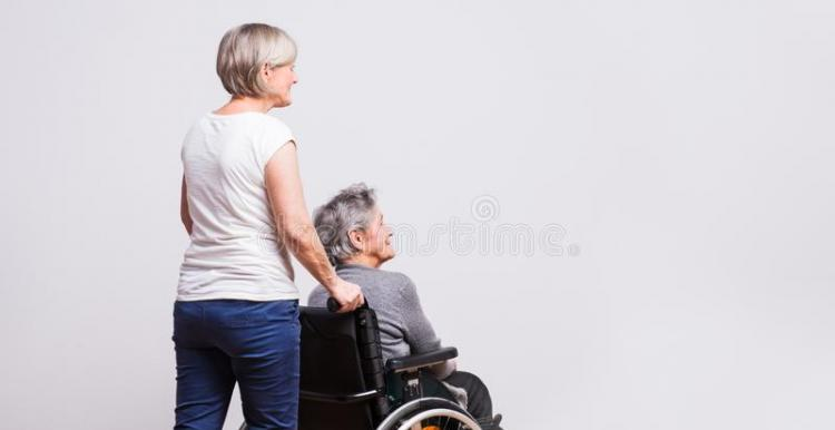 woman pushing older woman in wheelchair