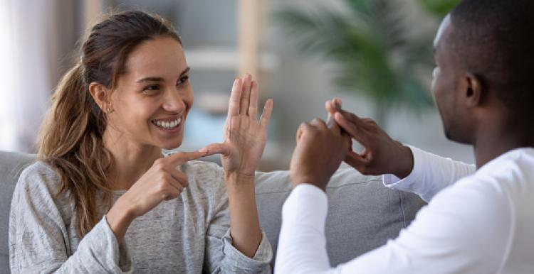 two people facing each other communicating in sign language