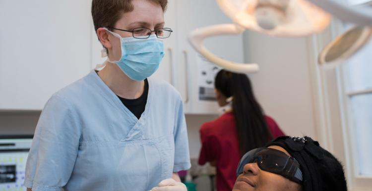 dentist standing treating patient in dental chair