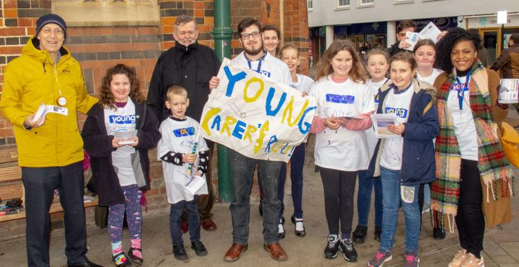 man holding young carers sign with group of young people