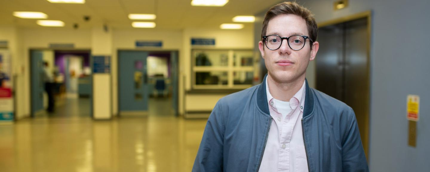 Young man standing face on to camera in a hospital hallway