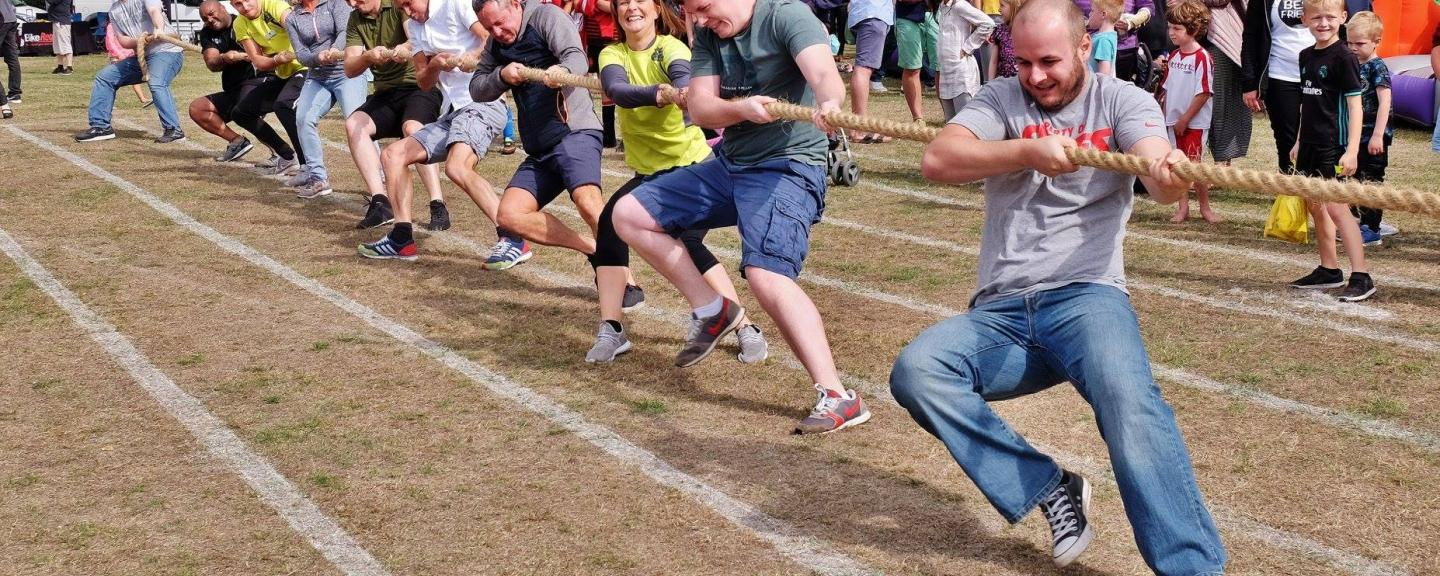men pulling rope in tug of war at community event