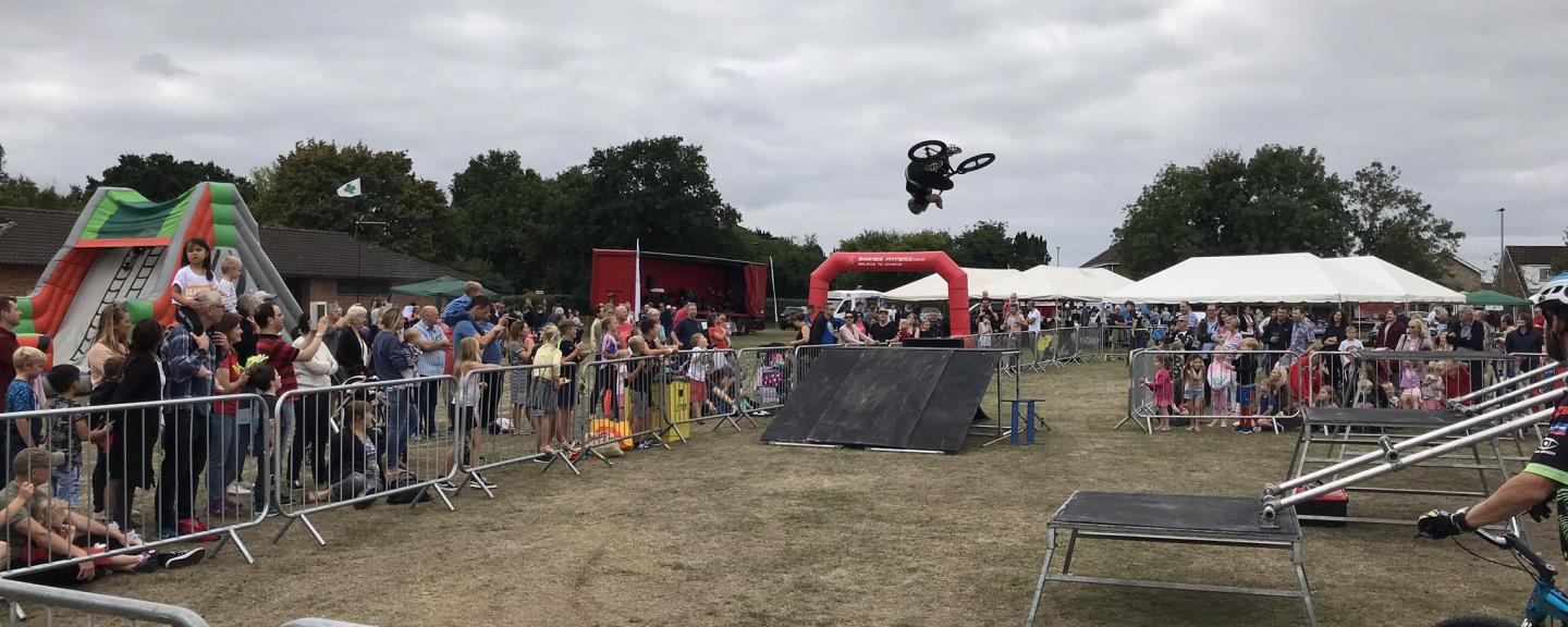 crowd of people watching bike jumping at community event