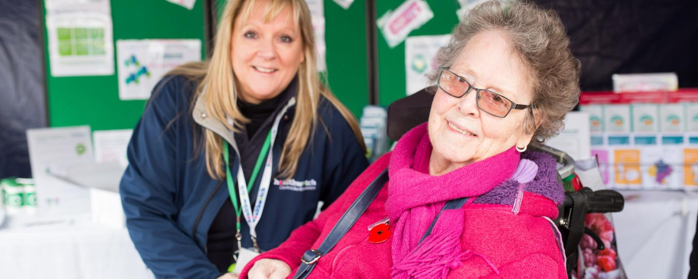 Healthwatch volunteer speaking to an elderly lady at an event