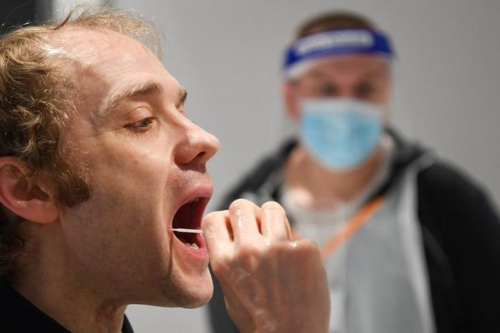man swabbing mouth for covid test