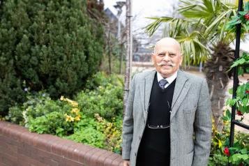 older man standing by walled garden holding a walking stick