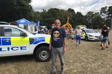 man standing in field next to police car at community event