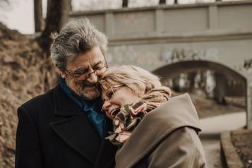 man and woman embrace and laughing on pathway near bridge