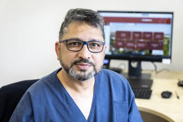 male doctor sat on chair at his desk looking at camera
