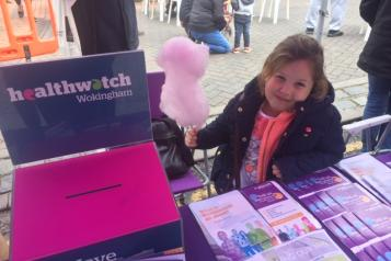 young girl with candy floss standing at table with leaflets on it