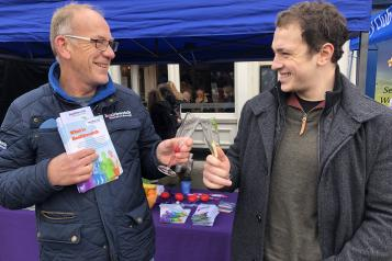 two men talking with each other with leaflet in hand