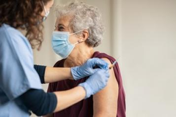 seated woman receiving covid vaccination in arm from a female nurse
