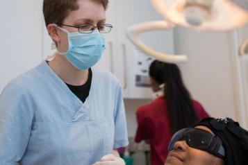 dentist communicating with patient sat in dental chair