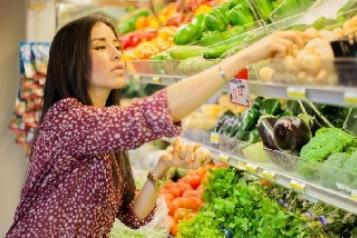 lady choosing vegetables in a shop