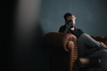 A man sitting on a sofa with his head in his hands