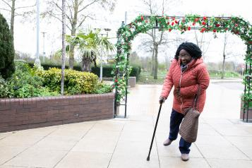 woman walking outside with aid of a walking stick
