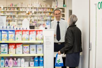 lady standing in pharmacy talking to a male pharmacist