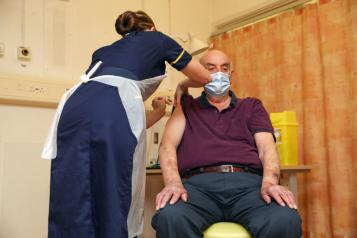 seated older gentleman in hospital having vaccine injection from a female nurse
