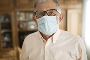 man wearing glasses in a room wearing face mask