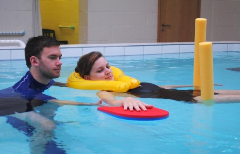 adult helping child exercise in a hydrotherapy pool